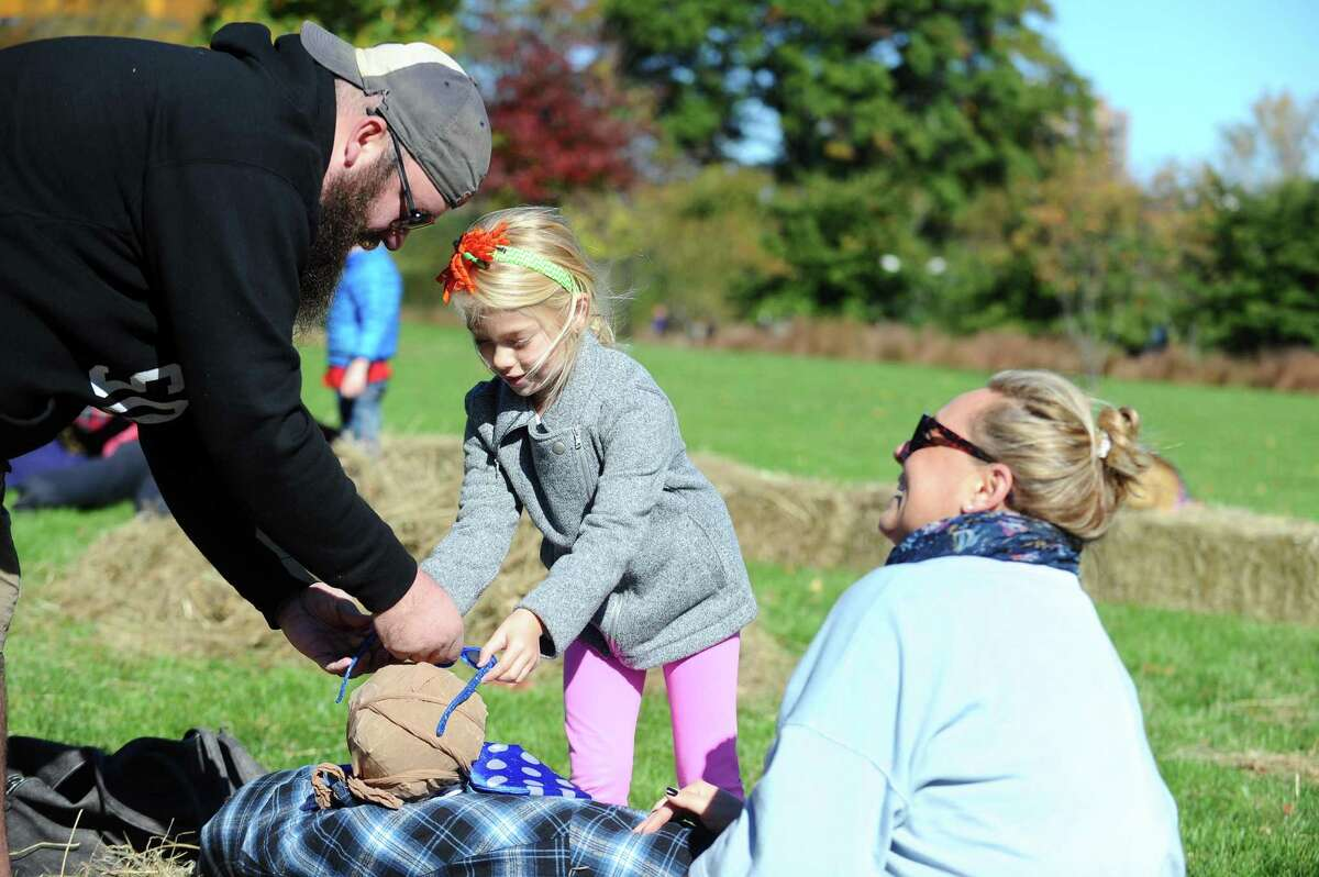Tessa Ritter, 6, works with her parents Krista and Jay Ritter to build a scarecrow during the Mill River Park Spooktacular in Stamford, Conn. on Sunday, Oct. 23, 2016.