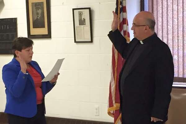Father Christopher Tiano is sworn in by City of Derby Mayor Anita Dugatto as the Derby Fire Department's first department-wide chaplain. Photo courtesy of the Derby Fire Department.