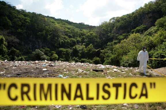 A forensic examiner walks along a garbage-strewn hillside above a ravine where examiners are searching for human remains in densely forested mountains outside Cocula, Guerrero state, Mexico, Tuesday, Oct. 28, 2014. Suspects arrested this week told prosecutors that many of the 43 students who disappeared Sept. 26 from the town of Iguala had been held near this location. (AP Photo/Rebecca Blackwell, Pool)
