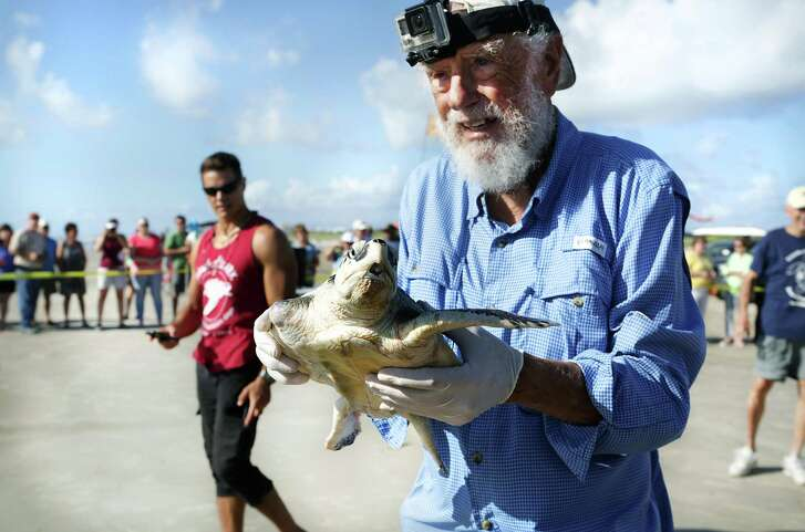 Amos carries a turtle to be released on a stretch of beach named for him. The turtle had lost a front flipper after being tangled in fishing line. Over the years, the ARK has rescued 700 sea turtles and returned many of them to the wild.