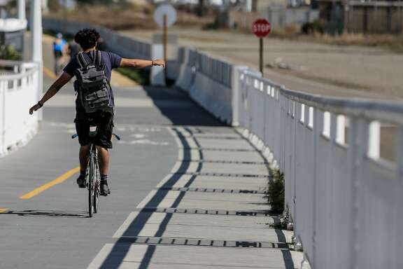 A man balanced himself on his bike, while riding along the 4.5-mile San Francisco-Oakland Bay Bridge path, which opened a new path today, connecting the Emeryville path with the new endpoint on Yerba Buena Island, in Oakland, California, on Sunday, Oct. 23, 2016.