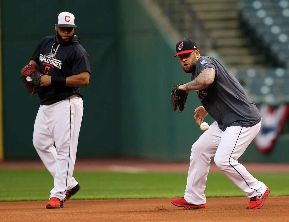 Cleveland Indians' Mike Napoli, right, fields a ball as Carlos Santana looks on during a team practice for baseball's upcoming World Series against the Chicag Cubs, Sunday in Cleveland. Photo: Aaron Josefczyk, FRE / FR171101 AP