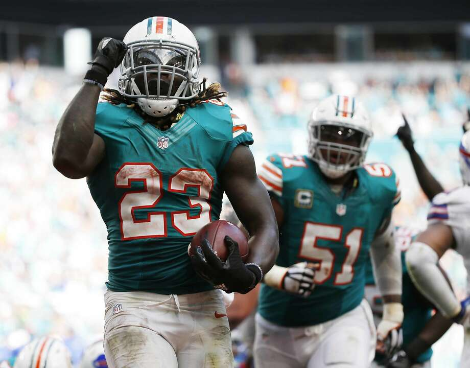 Miami Dolphins running back Jay Ajayi (23) celebrates a touchdown during the second half of an NFL football game against the Buffalo Bills, Sunday, Oct. 23, 2016, in Miami Gardens, Fla. To the right is Miami Dolphins center Mike Pouncey (51). (AP Photo/Wilfredo Lee) Photo: Wilfredo Lee, Associated Press