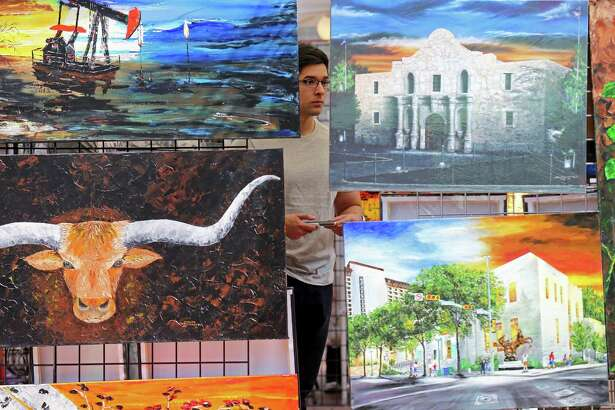 Guillermo Diego looks at paintings by artist Joseph Hernandez Jr. Sunday Oct. 23, 2016 in Market Square.