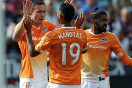 The Dynamo's Andrew Wenger, back left, is congratulated by teammates Mauro Manotas, front left, and Sheanon Williams after scoring in the first half.