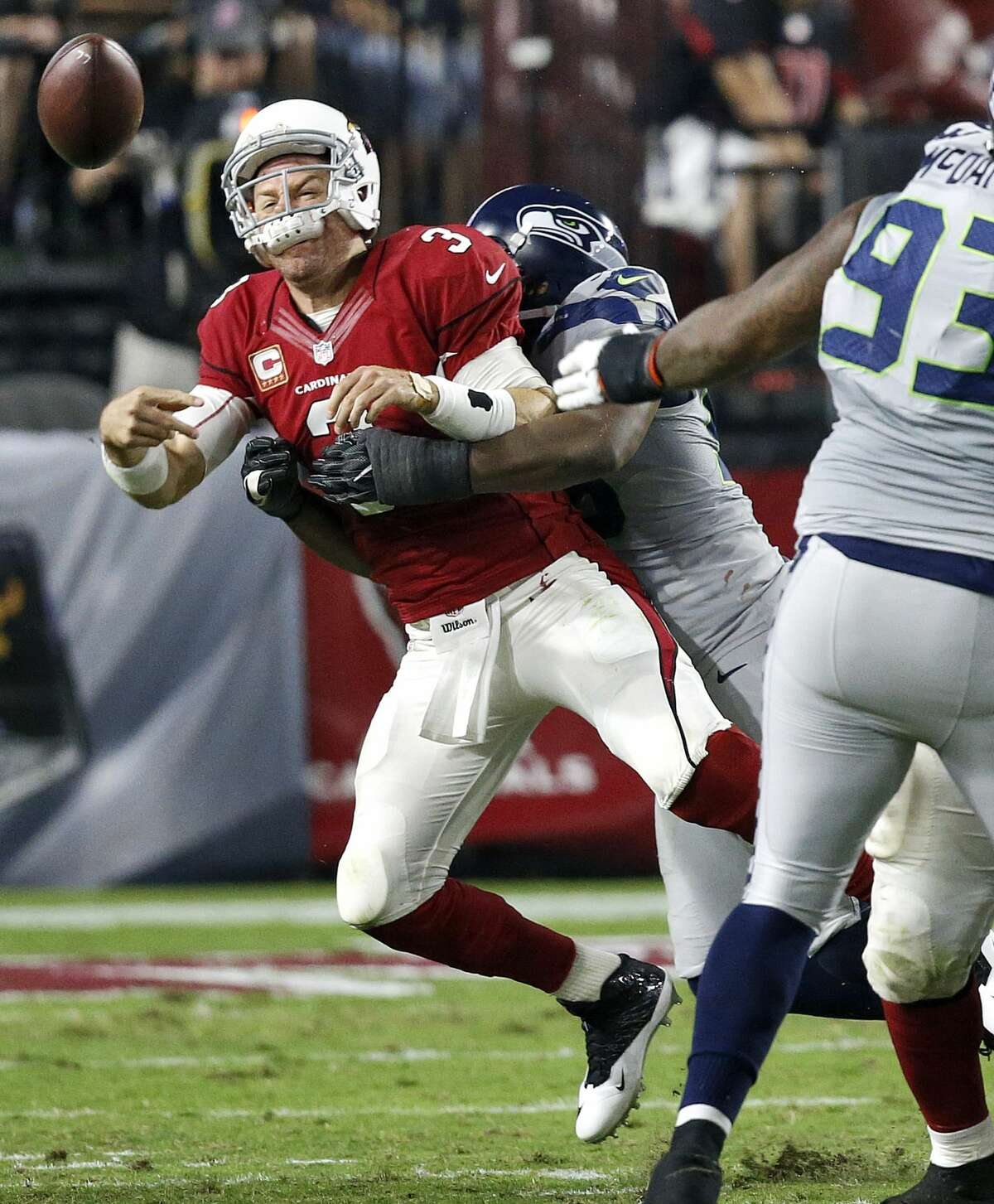 Arizona Cardinals quarterback Carson Palmer (3) his hit as he throws by Seattle Seahawks defensive tackle Ahtyba Rubin during the second half of a football game, Sunday, Oct. 23, 2016, in Glendale, Ariz. (AP Photo/Ross D. Franklin)