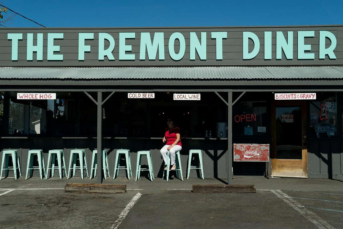 A woman sits outside the Fremont Diner in Sonoma, Calif. on Thursday, Oct. 20, 2016. The Fremont Diner is housed in a simple wooden building with picnic-style seating outside.