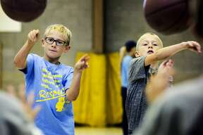 Blessed Sacrament School students Ben Marinik, 8, and Matthew Berg, 8, participate in a ball drill during a Health Fair/All Sports Day on Friday. Northwood University coaches and players partnered with Blessed Sacrament School to demonstrate how to play certain sports and to talk to students about sportsmanship, manners and nutrition.