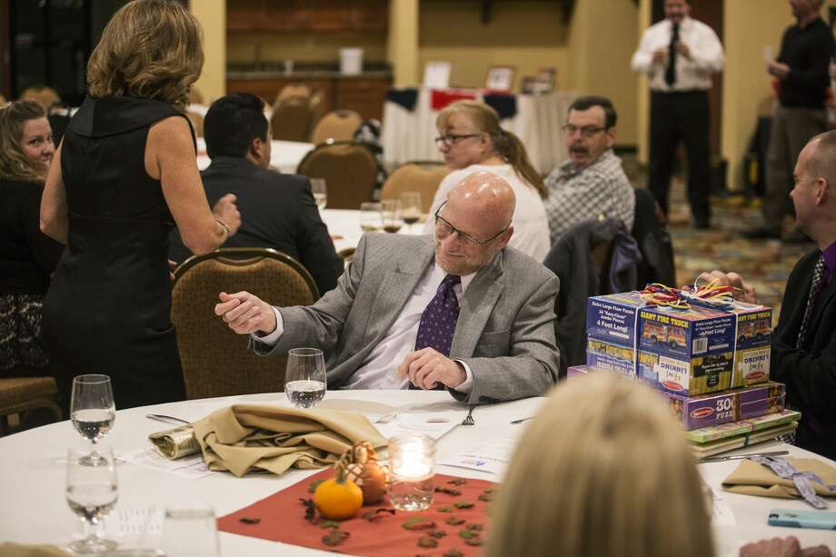 James Bicknell, President at Midland Emergency Room Corporation, reacts after Sue Kleinhans, of Midland, left, wins a raffle during the Midland Firefighter Youth Foundation Charity Ball at Holiday Inn on Saturday. Photo: Theophil Syslo