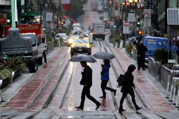 Pedestrians holding umbrellas walk in the street as rain falls in San Francisco on Oct. 14, 2016. Two storms were set to bring rain to the Bay Area this week.