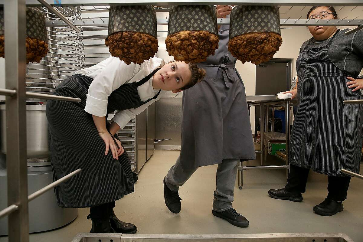 Sous chefs Lindsey Cameron (left) and Mary Ann Chou (right) check panettone just out of the oven on Thursday, October 20, 2016, in Richmond, Calif.