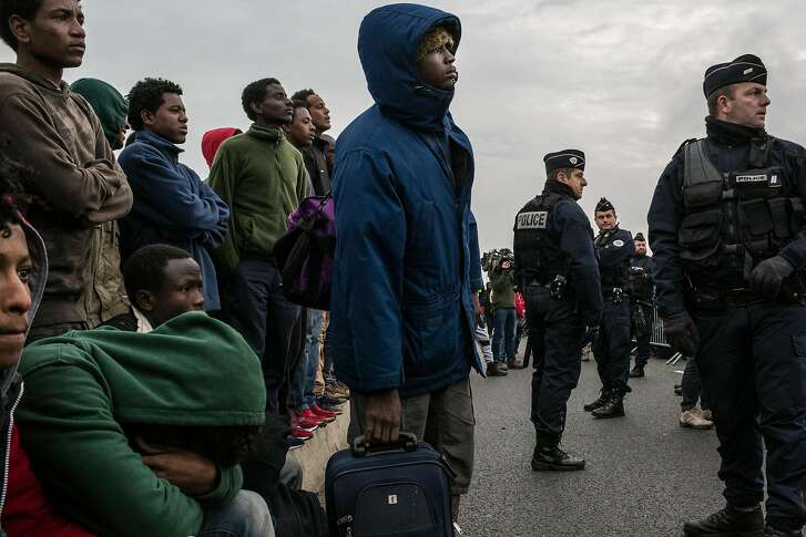 Refugees wait outside of a reception center to be registered, near the camp called the �Jungle,� in Calais, France, Oct. 24, 2016. France announced it will start to demolish the migrant camp that houses between 6,000 and 8,000 refugees from conflict-torn countries, prompting a mass dispersion to find temporary housing. (Mauricio Lima/The New York Times)