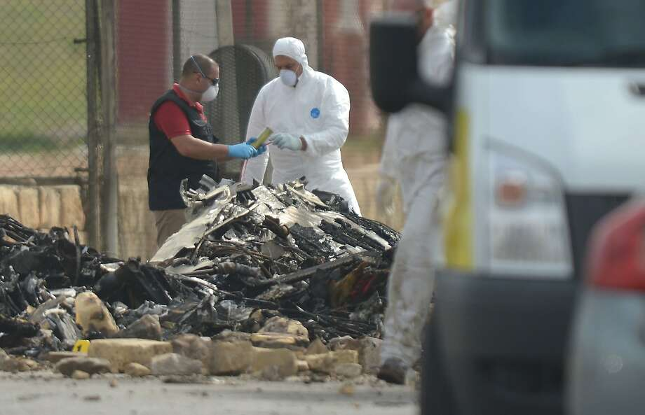 Aviation authorities examine debris from the crash of the small plane at Malta International Airport. Photo: Matthew Mirabelli, AFP/Getty Images