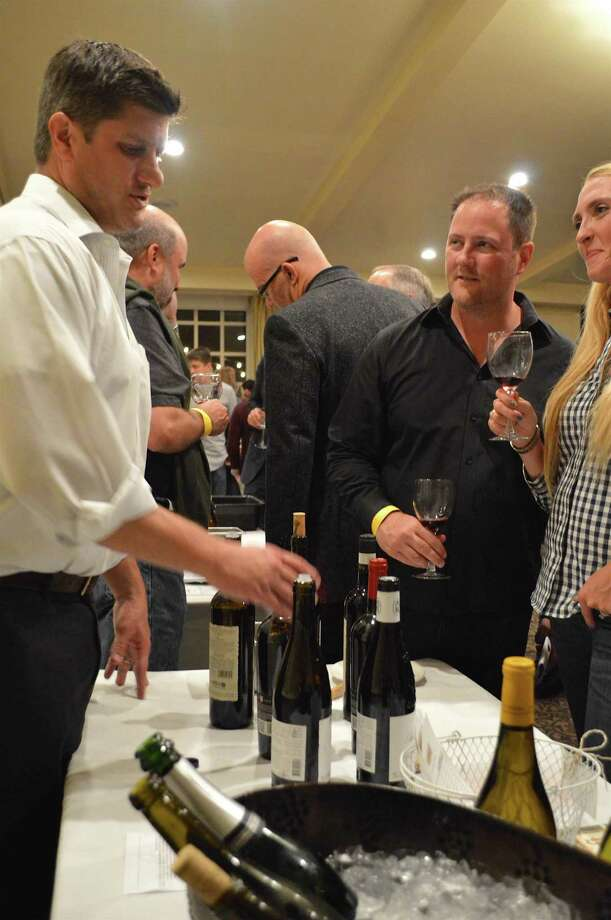 Andrew Clement of the Liquor Locker in Westport takes wine with Dan and Kelly Merton of Westport at the 26th annual Westport Uncorked gala, sponsored by Westport Sunrise Rotary, Friday, Oct. 21, 2016, at The Inn at Longshore in Westport, Conn. Photo: Jarret Liotta / For Hearst Connecticut Media / Westport News Freelance