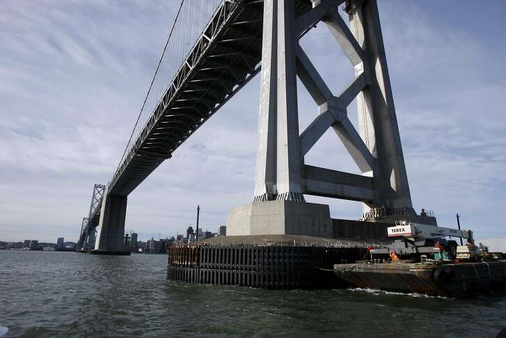 The Bay Bridge fender repair project on the delta tower  is done.The fender was damaged last month when the Cosco Busan side swiped it  FENDER_0014_KR.jpg Kurt Rogers / The Chronicle  Photo taken on 12/21/07, in San Francisco, CA, USA Ran on: 12-22-2007 Three weeks ahead of schedule and $500,000 under a $2 million budget, the Bay Bridge tower fender, above, clipped by the freighter Cosco Busan on Nov. 7 has been repaired, said Caltrans. The impact ripped a 230-foot gash in the port side of the ship and punctured fuel tanks on the 900-foot container ship, the first oceangoing vessel to hit the span. Some 58,000 gallons of fuel oil spilled in the bay and beyond, fouling beaches from Point Reyes to Pacifica, the worst such damage in a decade. The new fender on the second tower west of Yerba Buena Island is made of recycled plastic that contrasts with the old one, right, made of wood. California Engineering Contractors of Pleasanton, the company that built the fenders as part of an upgrade to the bridge piers a year ago, performed the repair work.