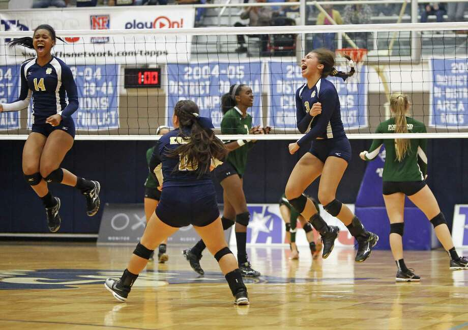 Holy Cross' Brie-anna Armstrong and Henrianna Ibarra (right) react after a point in a TAPPS 4A state semifinal volleyball match at South San High School on Nov. 13, 2015. Photo: Ron Cortes /For The Express-News