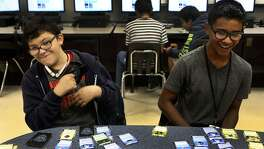 "Ronald McNair Middle School students John Salas,13, (left) and Trey Cano (right),12, play a card game Thursday October 20, 2016 called Cyber Threat Defender that was developed by a professor at the University of Texas at San Antonio to teach young students about cyber security. Teacher Michael Maldonado says the game teaches students ""how to build a network and defend a network."" McNair Middle School is in the Southwest Independent School District."