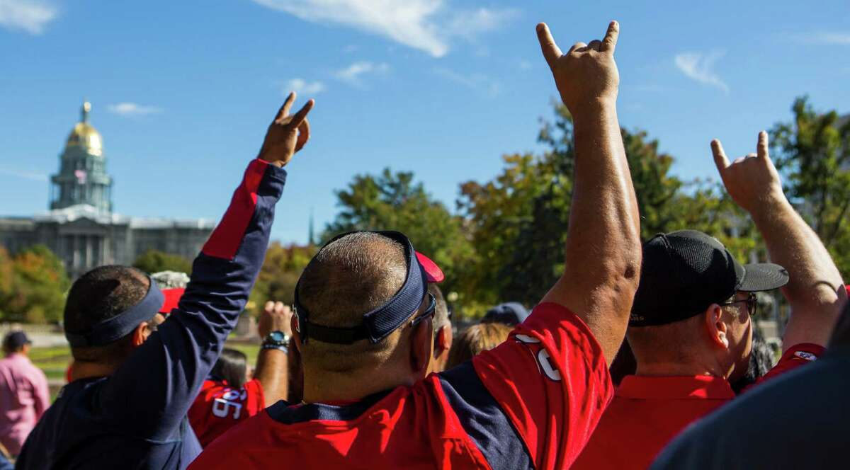 Houston Texans fans pose for a photo in Civic Center Park near the Colorado Statehouse during a gathering of the Traveling Texans on Monday, Oct. 24, 2016, in Denver.