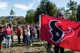 Houston Texans fans pose for a photo in Civic Center Park during a gathering of the Traveling Texans on Monday, Oct. 24, 2016, in Denver.