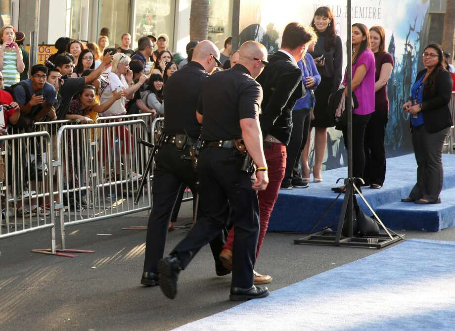 """Journalist Vitalii Sediuk is walked off carpet in handcuffs after allegedly attacking Brad Pitt at the world premiere of """"Maleficent"""" at the El Capitan Theatre on Wednesday, May 28, 2014, in Los Angeles. Sediuk's antics have left him with fewer friends in the entertainment world after his publicist and television station cut ties with him over pranks that have once again landed the 25-year-old in handcuffs. He's kissed Will Smith in Moscow, tried to steal Adele's spotlight at the Grammys, dove under America Ferrera's dress at Cannes and now accosted Pitt on the red carpet of a Hollywood premiere. (Photo by Matt Sayles/Invision/AP)"""