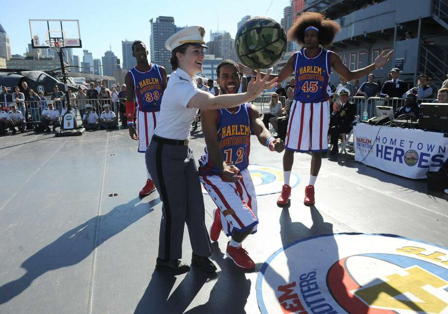 "In this image taken Monday, Oct. 6, 2014 in New York, the World Famous Harlem Globetrotters teach West Point Cadet Captain Julie Dillon, of Stafford Springs, Connecticut, how to spin the ball during an exhibition game on the flight deck of the Intrepid Sea, Air & Space Museum. The Globetrotters played the exhibition game to announce the dates for their 2014-15 North American Tour, during which they will honor a ""Hometown Hero,"" a current or past member of the U.S. armed forces, at each stop on their tour. (Photo by Diane Bondareff/Invision for the Harlem Globetrotters/AP Images)"