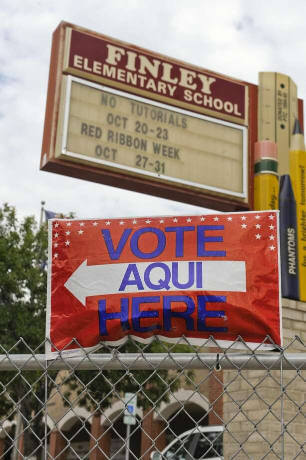"""A """"Vote Here"""" sign sits on the fence of Finley Elementary on Monday afternoon. More than 1,600 Webb County voters hit the polls in the first day of early voting for the Nov. 4 general election. READ MORE: http://bit.ly/1ycLx3H (Photo by Danny Zaragoza/Laredo Morning Times)"""
