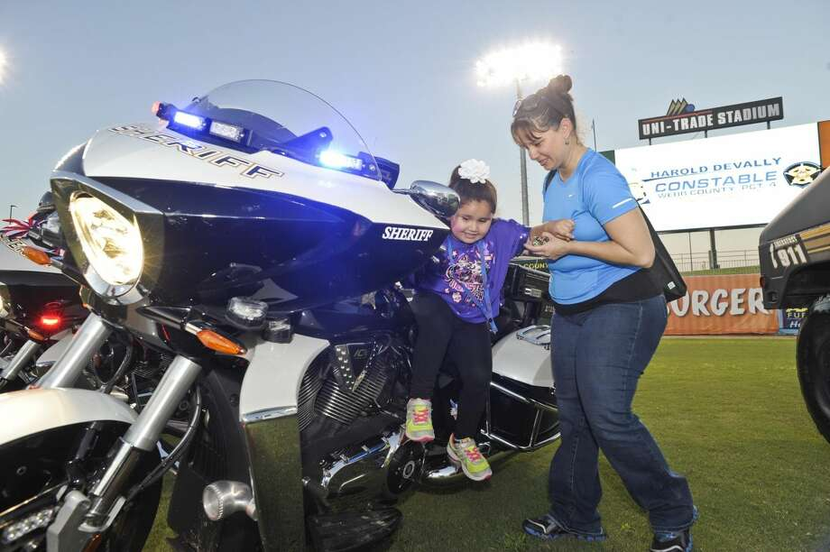 Mia Reyes recibe la ayuda de su madre, Sara Reyes, para descender de una motocicleta de la Oficina del Alguacil del Condado de Webb, en octubre del 2013, durante el evento National Night Out. (Foto de archivo/LMT)