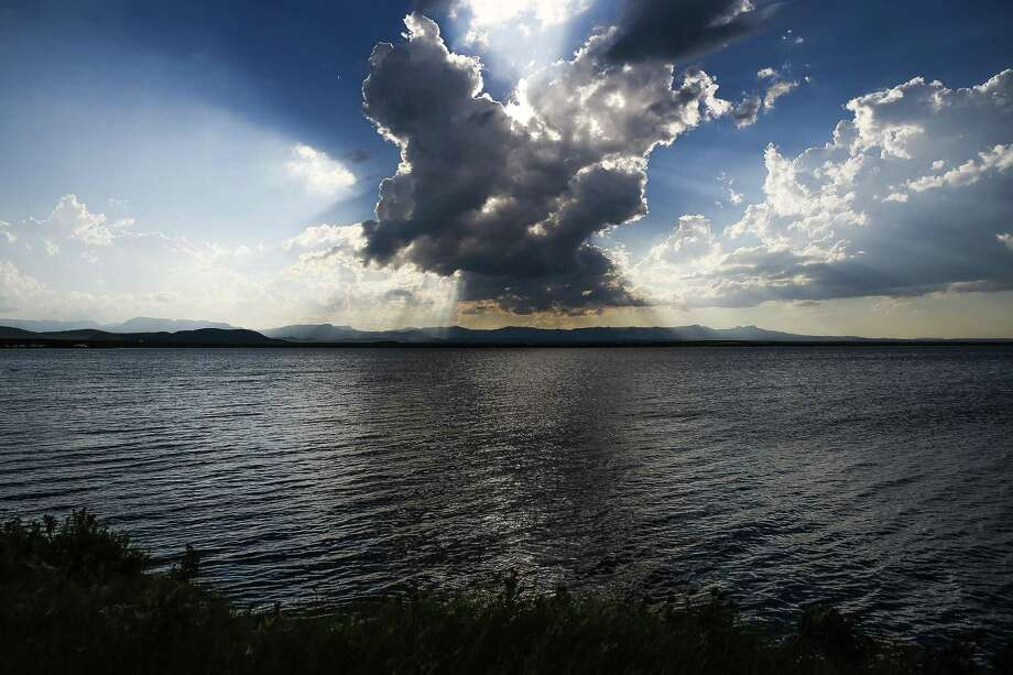 The sun sets behind a cloud over Balmorhea Lake. A growing number of environmental organizations are scrutinizing plans by Houston-based Apache Corp. to drill for oil and gas around West Texas' popular Balmorhea State Park and its famous spring-fed pool. Photo: Michael Ciaglo /Houston Chronicle / © 2016  Houston Chronicle