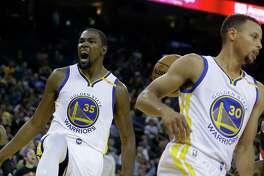 Golden State Warriors' Kevin Durant, left, celebrates after scoring against the Portland Trail Blazers during the second half of a preseason NBA basketball game against the Portland Trail Blazer last week in Oakland, Calif. At right is Warriors' Stephen Curry (30).