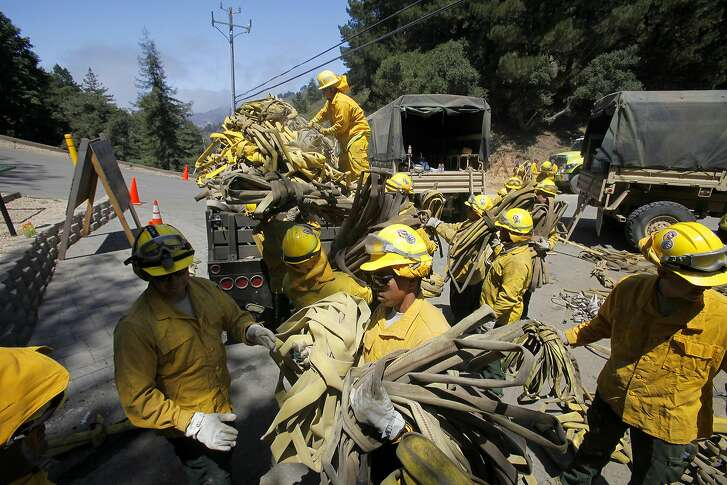 Members of the California National Guard help load about 5 miles of used wildland fire hose in Palo Colorado Canyon, south of Monterey Calif., on Saturday, Aug. 6, 2016, during efforts to fight the Soberanes Fire (Vern Fisher/The Monterey County Herald via AP) MANDATORY CREDIT