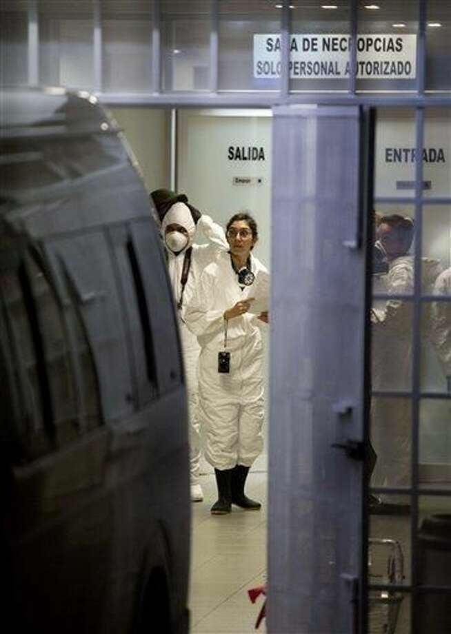 Forensic workers stand inside of the morgue in Iguala Mexico, Sunday Oct. 5, 2014. Mexican forensic experts recovered 28 charred bodies from a clandestine grave on the outskirts of this city where police engaged in a deadly clash with student protesters a week ago, Guerrero state's chief prosecutor said Sunday. READ MORE: http://bit.ly/ZPmCbb (AP Photo/Eduardo Verdugo)