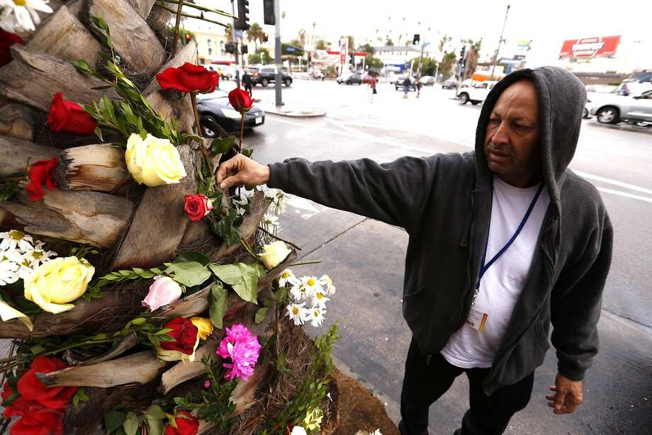 Gabriel Urano places a tribute on a memorial for the victims of the bus crash near Palm Springs. Photo: Al Seib, TNS