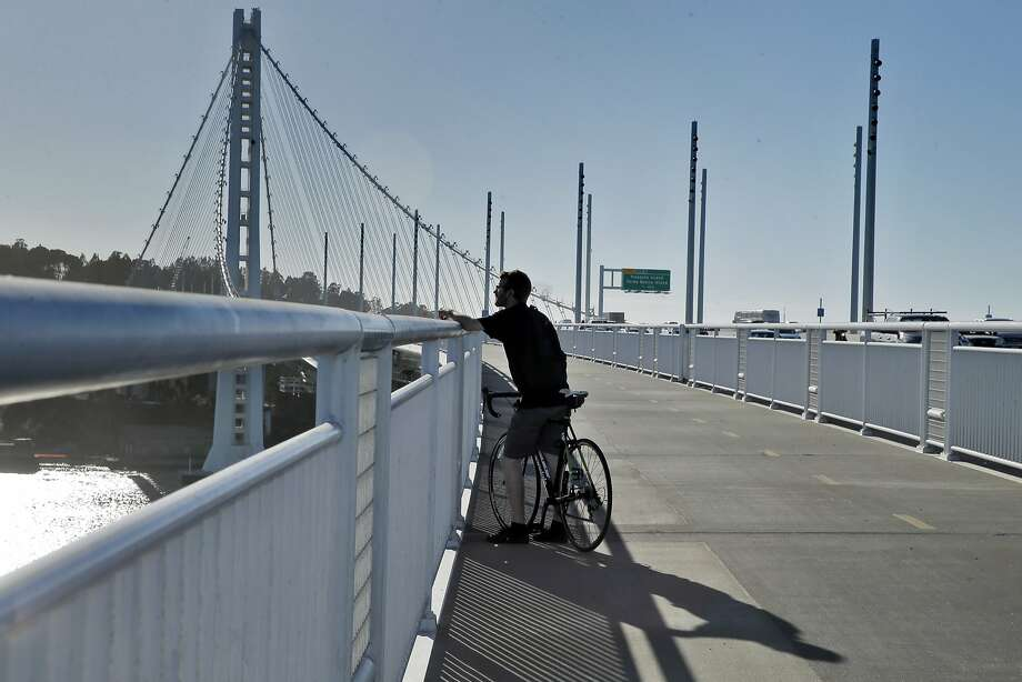 Andy Roth of Berkeley, looks out over the demolition of the old Bay Bridge from the new bridge's bike and pedestrian path in Oakland, Calif., on Thursday, Oct. 29, 2015. The Bay Bridge bike path from Oakland to Yerba Buena Island is likely to be available for use on weekday after a series of delays, a BART official said Thursday, March 9, 2017. Originally scheduled to open with the new eastern span four years ago, the plan was put on hold for safety reasons while demolition of part of the old span could be completed. The path is currently open only on weekends and holidays. Photo: Carlos Avila Gonzalez, The Chronicle