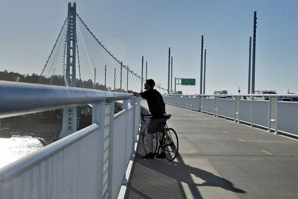 Andy Roth of Berkeley, looks out over the demolition of the old Bay Bridge from the Bicycle Pedestrian Path in Oakland, Calif., on Thursday, October 29, 2015. The Bay Bridge bike path from Oakland to Treasure Island has been delayed yet again. Originally scheduled to open along with the new eastern span two years ago, completion had to wait for demolition of part of the old span, which was to be completed by summer. Then it was delayed until late fall/end of the year. Now, it looks like bike riders won't be able to pedal from the East Bay to Treasure Island until sometime next year.