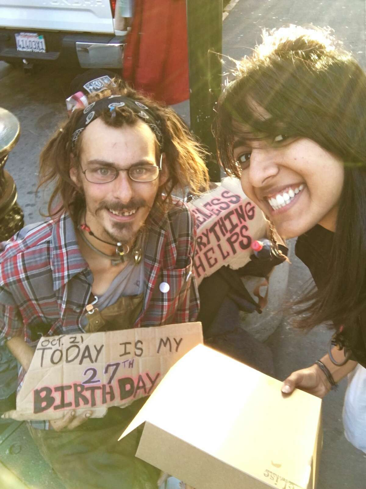Deepika Phakke connects with a man living on the street in San Francisco. WhenPhakke noticed his sign saying it was his birthday, she gave him a cupcake.
