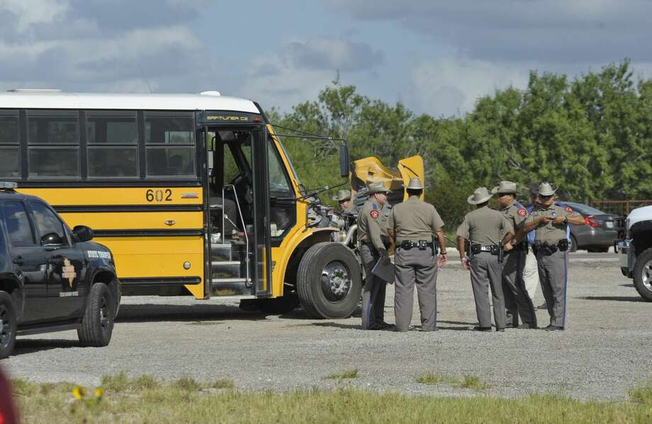 Texas State Troopers speak among themselves Tuesday afternoon after assessing the damage done to a school bus after a red Chevy Silverado collided with the bus on Highway 359 near Mirando City. (Photo by Danny Zaragoza