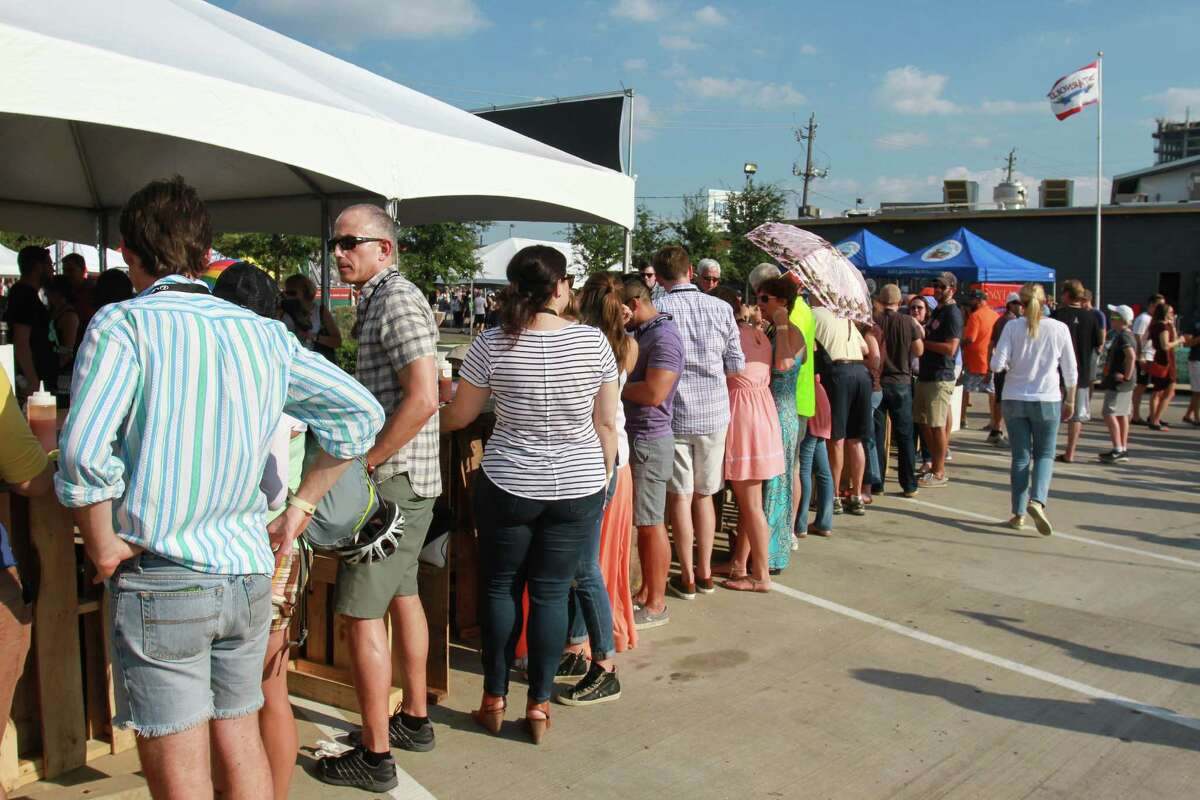 People eating at a long table at Southern Smoke, a huge barbecue event sponsored by Underbelly. (For the Chronicle/Gary Fountain, October 11, 2015)