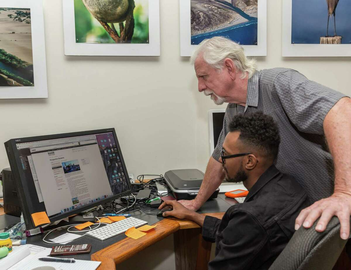 October 21 2016: Ryan Hollaway examines one of many images used in violation of copyright with Jim Olive, owner of Stockyard Photos located n Houston, Texas. (Leslie Plaza Johnson/Chronicle)