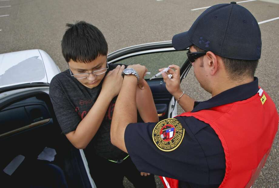 Daniel A. Bustamante receives his flu shot from EMT Jesus Tapia during a drive-thru clinic at the Laredo Energy Arena in November 2013. (File photo by Victor Strife/Laredo Morning Times)