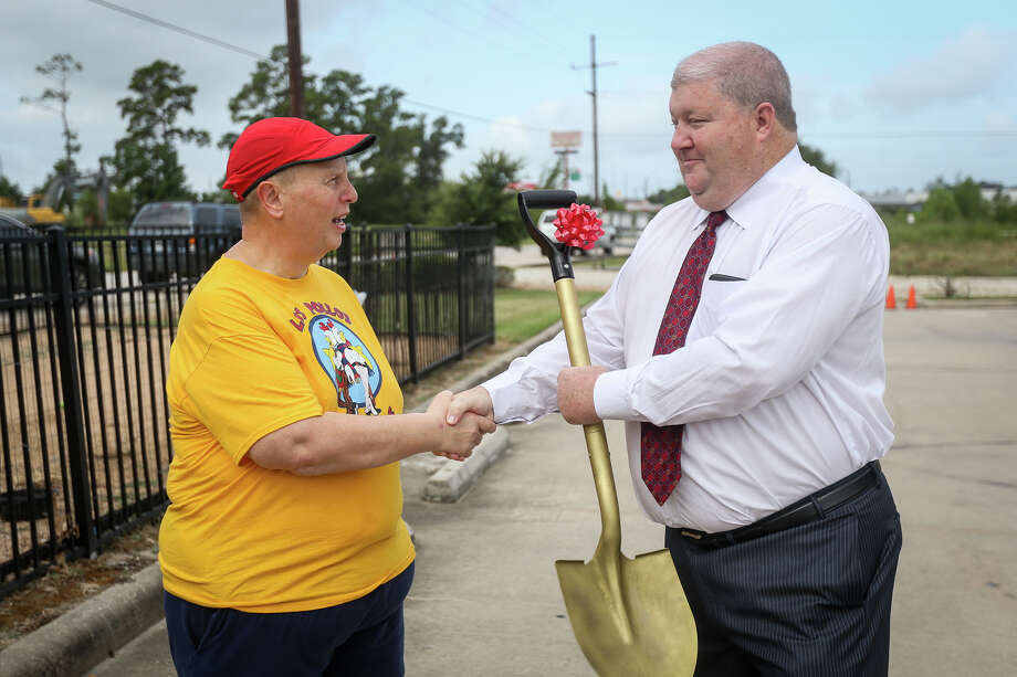 Eric Yollick shakes hands with Pct. 4 Commissioner Jim Clark while presenting him with a golden shovel on Friday, Aug. 12, 2016, at the Montgomery County Animal Shelter. Photo: Michael Minasi, Photographer / Copyright 2014 Michael Minasi