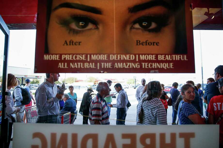 Hundreds of people pass by Maharani's Beauty Salon as they wait in line to cast their ballot at the Fiesta Mart off Kirby Drive during the first day of early voting Monday, Oct. 24, 2016 in Houston. Photo: Michael Ciaglo, Houston Chronicle / © 2016  Houston Chronicle