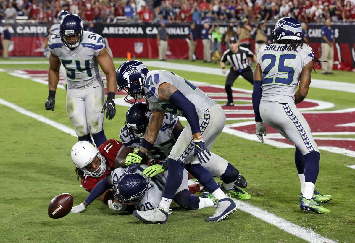 Seattle Seahawks cornerback Richard Sherman, free safety Earl Thomas, middle linebacker Bobby Wagner strong safety Kelcie McCray and cornerback Jeremy Lane knock the ball away from Arizona Cardinals wide receiver Larry Fitzgerald as overtime expires during an NFL football game, Sunday, Oct. 23, 2016, in Glendale, Ariz. The game ended in overtime in a 6-6 tie. (AP Photo/Ross D. Franklin)