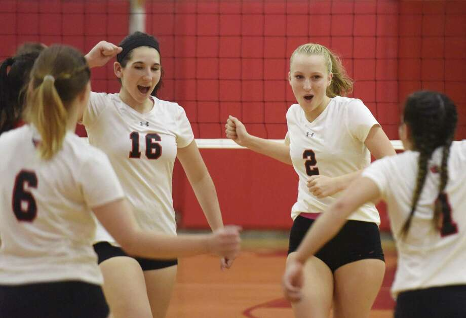 Greenwich's Morgan Rafferty (16) and Amelia Bartlett (2) celebrate with teammates after scoring a point in Greenwich's 3-0 win over Danbury in the high school girls volleyball match at Greenwich High School in Greenwich, Conn. Monday, Oct. 24, 2016. Photo: Tyler Sizemore / Hearst Connecticut Media / Greenwich Time
