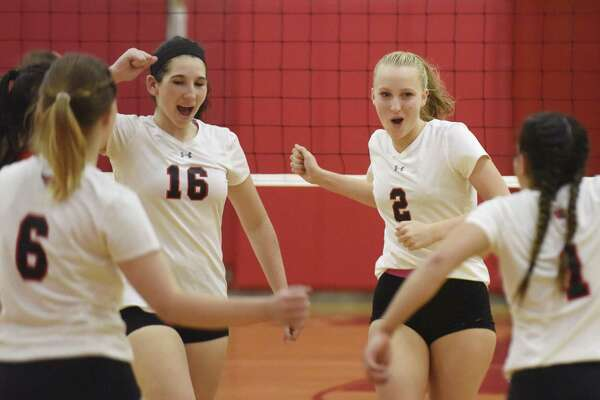 Greenwich's Morgan Rafferty (16) and Amelia Bartlett (2) celebrate with teammates after scoring a point in Greenwich's 3-0 win over Danbury in the high school girls volleyball match at Greenwich High School in Greenwich, Conn. Monday, Oct. 24, 2016.