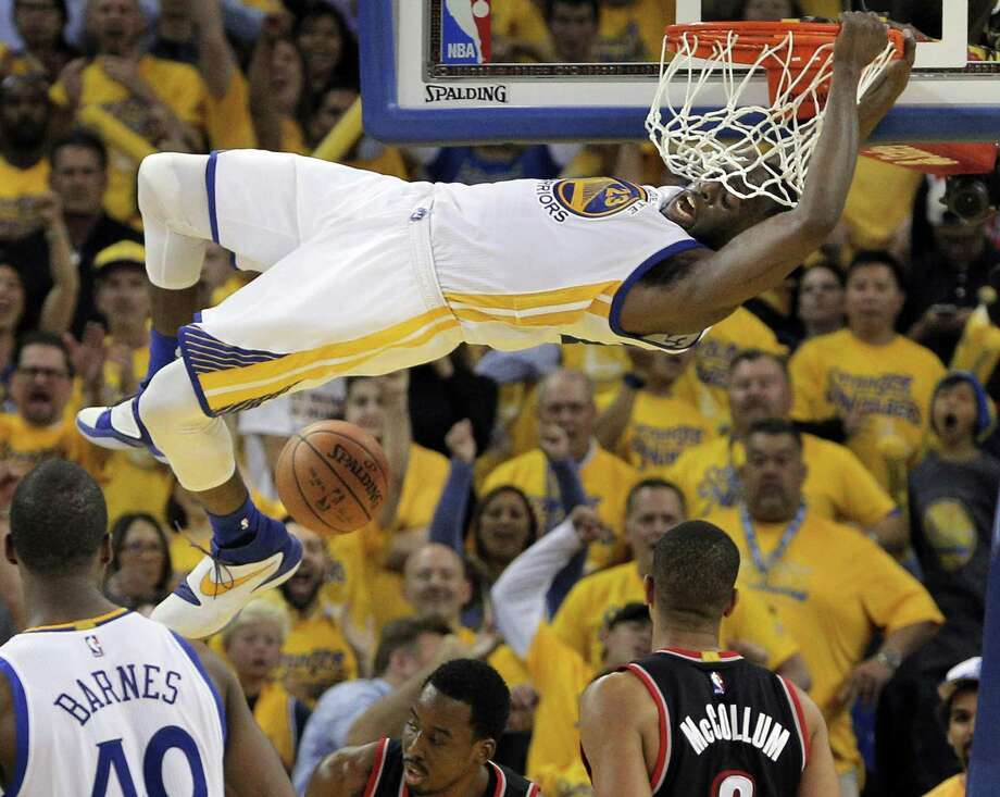 Draymond Green hangs on the rim after a dunk during the Warriors' win over the Trail Blazers in Game 2. Photo: Carlos Avila Gonzalez / Carlos Avila Gonzalez / The Chronicle / San Francisco Chronicle/Carlos Avila Gonzalez