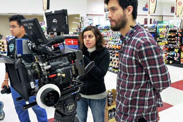 "Filmmakers Rainia Attieh, center, and Daniel Garcia, right, film a scene of their movie ""H"" in the Price Chopper in Brunswick Plaza Thursday March 13, 2014, in Troy, NY.  (John Carl D'Annibale / Times Union)"