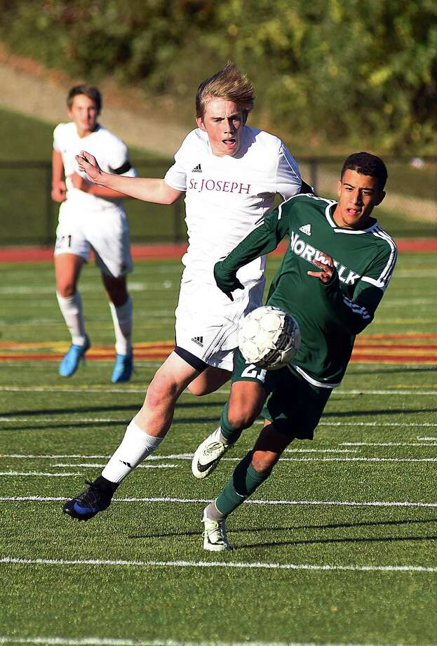 Norwalk's Maicol Ruiz, right, races St. Joseph's Owen Francis to a ball during Monday's FCIAC boys soccer regular season finale between the two schools in Trumbull. Norwalk posted a 6-0 win over the Cadets to clinch a state tournament spot. Photo: John Nash / Hearst Connecticut Media / Norwalk Hour