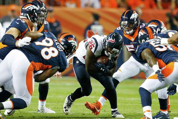 Houston Texans running back Lamar Miller (26) runs through a hole during the first quarter of an NFL football game at Sports Authority Field at Mile High on Monday, Oct. 24, 2016, in Denver.