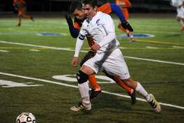 Fairfield Ludlowe's David Bates races the ball upfield chased by a Danbury defender during their boys soccer game at Ludlowe High School in Fairfield on Monday.