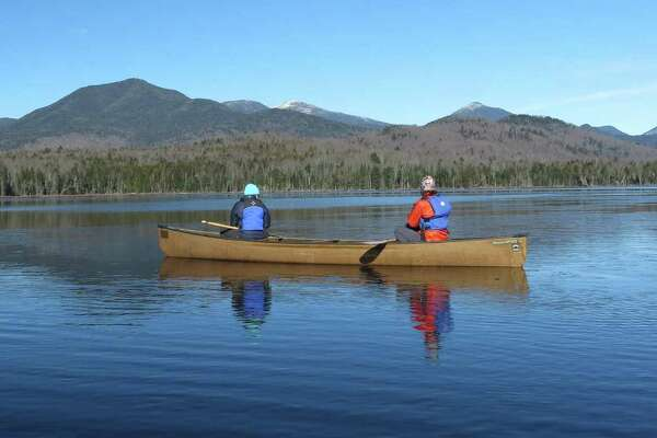 In this photo taken on Tuesday, Nov. 17, 2015, Connie Prickett, right, of The Nature Conservancy, takes a guest on a canoe tour of Boreas Pond in North Hudson, N.Y. (AP Photo/Mary Esch)